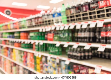 Blurred image of soft drinks aisle in American supermarket. The affordability and wide variety of sugary drinks contribute to the growing obesity problem in the U.S. Drink bottles display on shelves