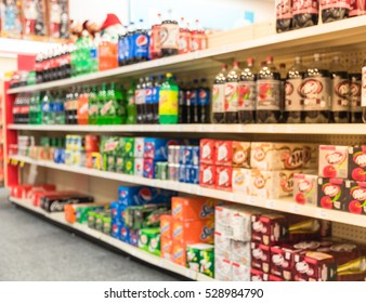 Blurred image soft drinks aisle in American store. The affordability, wide variety of sugary drinks contribute to the growing obesity problem in U.S. Fuzzy drink bottles display on supermarket shelves