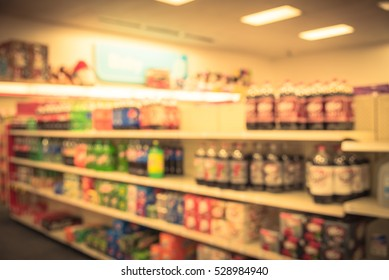 Blurred image soft drinks aisle in American store. The affordability, wide variety of sugary drinks contribute to the growing obesity problem in U.S. Fuzzy drink bottles on display. Vintage filter.