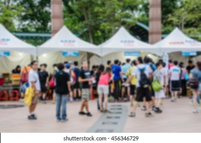 Blurred image of sport and festival events with people before white tents.