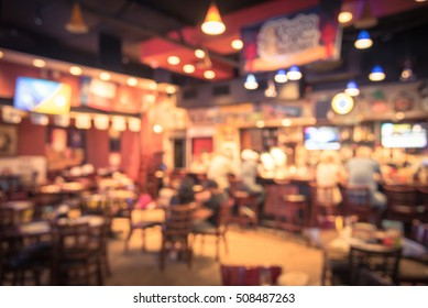 Blurred image sport and gumbo, oyster bar with TV, classic counter, tables and chairs in Houston, Texas, US. Bar Happy Hour, dine in abstract background. Night club, grill bar concept. Vintage filter.