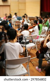 Blurred image of students practicing in school string orchestra