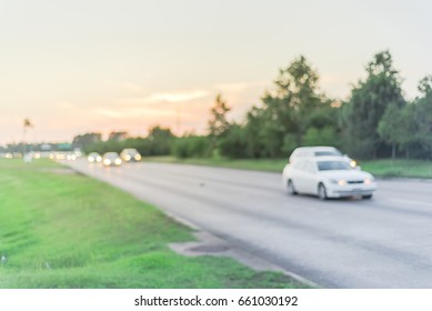 Blurred image of traffic and defocused bokeh lights at rush hour during sunset. Out of focus traffic in afternoon rush hour at Humble, Texas, US. Line of cars at peak travel time. Urban infrastructure