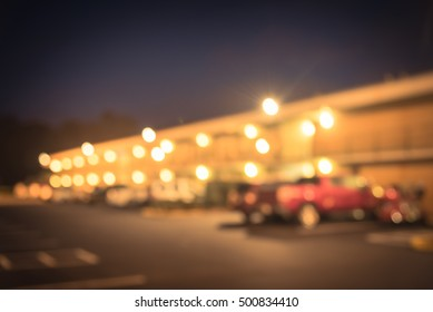 Blurred image of two story motel with parking lot in foreground at blue hour in Hope, Arkansas, US. Generic budget motel in suburban roadside location with row parked car next to room. Vintage filter.