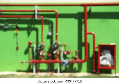 Blurred image of water sprinkler and fire alarm fighting system with green wall and sunlight. Used as background.