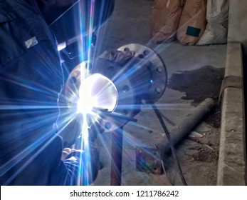 Blurred image, Welder argon welding flanges to the pipe stainless steel by a method of manual arc welding, with beautiful light.