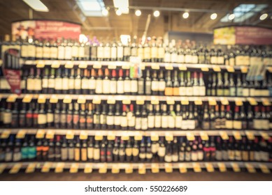 Blurred image wine shelves with price tags on display at store in Humble, Texas, US. Defocused rows of Wine Liquor bottles on supermarket shelf. Alcoholic beverage abstract background. Vintage tone