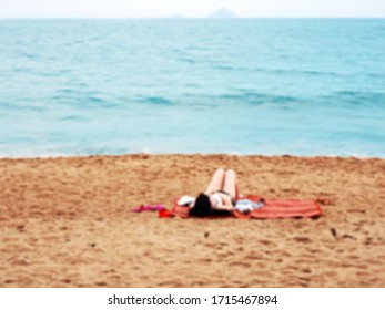 blurred image of woman in swimsuit lie down on red mat for sunbath and relax on sand blue sea beach
