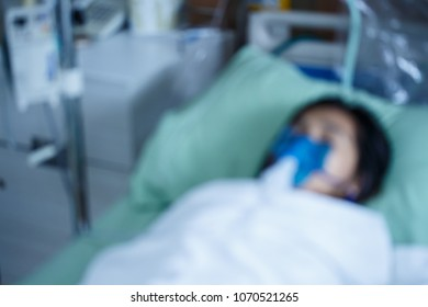 Blurred image of a woman using inhalation mask for asthma and respiratory on the bed in hospital
