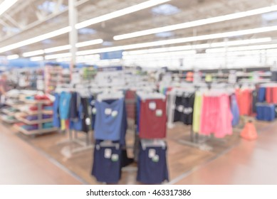 Blurred image of women wear department store in a hypermarket. Wide perspective view of empty supermarket aisle, defocused blurry background with bokeh light in store. Business concept.