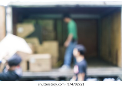 Blurred image of workers lifted carton from the truck, for background uses