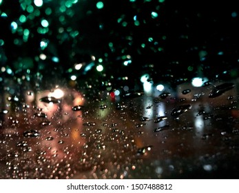 Blurred image,colorful bokeh with street light at night,raindrop on car windshield.Driving car in heavy rain storm.Traffic in the city on a rainy day.