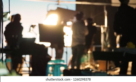 Blurred images of behind the scenes of filming or movie shooting or video production for online commercial and crew teams setting up light and prop and blue screen for next shot of camera recording