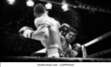 Blurred images black and white photo style of Thai boxing or Muay Thai or Kickboxing which local and foriegn boxer are fighting on the ring at indoor stadium stage as a martial art sport
