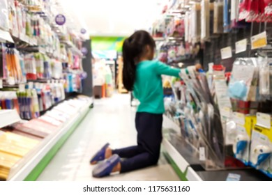Blurred images of children are shopping for stationery.