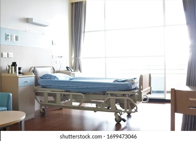 Blurred images of hospital patients room with adjustable beds, blue sofas. Spacious rooms without people.
