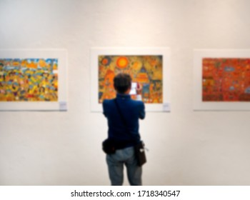 Blurred images of a man is watching an art exhibition in the art gallery.