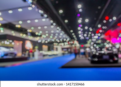 Blurred images of motor shows that are full of people and lights.