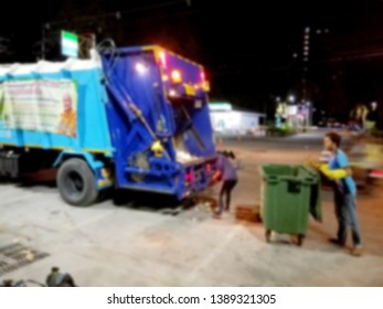 Blurred images of municipal garbage collectors are picking up garbage in the garbage truck at night without anyone.