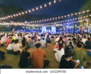 Blurred images of people sitting on the field  To see the concert  And join the activity at night