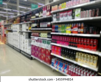 Blurred images of shelves in store with an assortment of bottles of liquor from various manufacturers. Beverage shelf in department store, alcoholic beverages, red wine on the shelves.