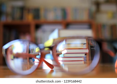 Blurred images of stacked books viewed from the reflection of the glasses