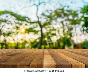 Blurred images of wood table and forests with the sky as a backdrop.