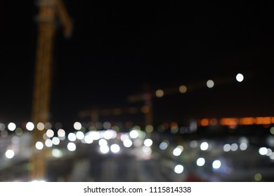 Blurred of Industrial Construction cranes with Abstract Circle Bokeh Blur background in night light.Industry and Technology concept.