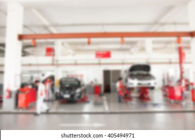 Blurred of inside car garage with cars being under maintenance and technicians for background