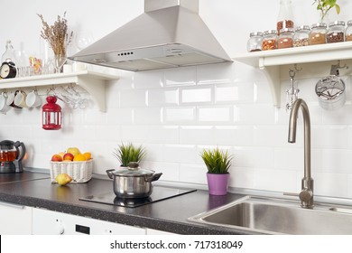 Blurred interior of a light kitchen in the apartment. Bright home interior decoration items, fruit, flowers in a pot, steel hood. Bright ready-made picture for your individual design