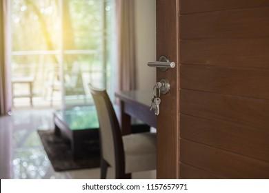 Blurred interior living space behind door opened. Door half opened in front of blur interior. Selective focus.