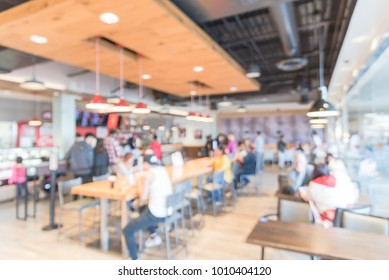 Blurred interior modern hipster cafe, open coffee shops, self-serve bakeries in USA. People queuing behind stanchion barriers check-out and sitting enjoy pastry, drink. High bar table, natural light