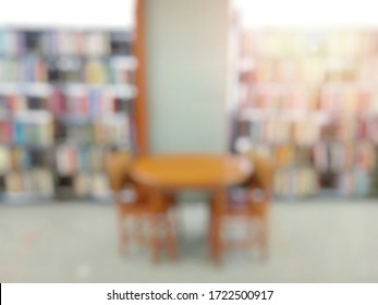 Blurred of the interior of the public library with wooden tables, chairs and books in bookshelves. Education and book's day background concept.