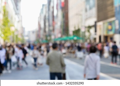 Blurred Japanese and Foreign tourists are Walking across the crosswalk around Ginza Wako and Ginza Mitsukoshi upmarket in Tokyo, Japan.