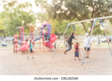 Blurred kids on swing at busy public playground in Katy, Texas, USA. Defocused children, parents doing activity together. Hanging seat suspended from bar back, forth. Colorful playground in background