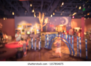 Blurred kids and parents playing at science educational museum in America