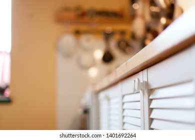 Blurred kitchen background and white cupboard with wooden shutter doors. Stylish cabinet with louver slats. Cozy home scene and atmosphere hygge. Warm light.