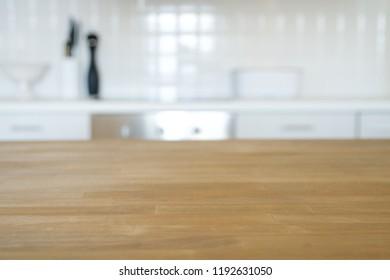 Blurred kitchen background. Wooden tabletop and Modern light kitchen