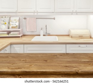 Blurred kitchen interior with wooden dinning table in front
