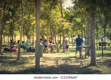 Blurred large group of friend, family members enjoy barbecue on lakeside area. Outdoor camping at natural park with picnic table in Grand Prairie, Texas, USA. Outside Party and BBQ Concept