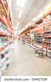 Blurred large hardware store in America. Defocused interior home improvement retailer, racks, rows of interior paint, exterior paint/stain, floor paint/stain cans and building materials up to ceiling.
