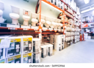 Blurred large hardware store in America. Defocused interior home improvement retailer, racks, rows of toilet seats, bowls, bidets, lids, ducting, water heaters and building materials. Vintage tone.