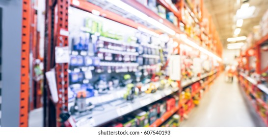 Blurred large hardware store in America. Defocused interior home improvement retailer, racks of various power tools, cordless kit router, sander, cordless drills and building material. Panorama style.