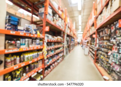 Blurred a large hardware store, tools and material. Defocused interior home improvement retailer with racks of door hardware, weather proofing and lockset from floor to ceiling. Construction wholesale