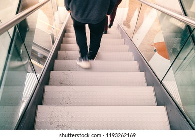 the blurred legs of a person go down a staircase