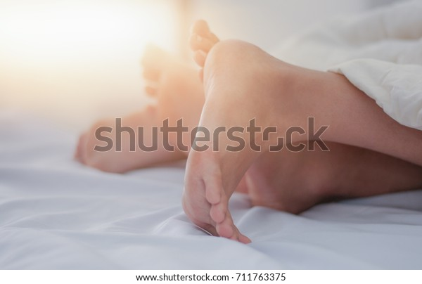 Blurred Legs view Couple's feet of two Lover's Morning light in bed at home on holiday concept having sexual romantic moments Women are offensive on top Warm contrast filter