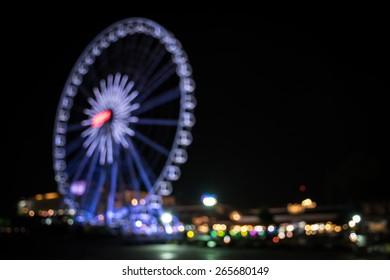 Blurred light of ferris wheel in Bangkok , Thailand - Blurred defocused night lights