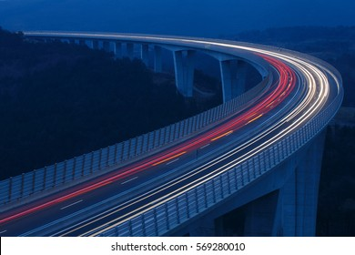 Blurred lights of vehicles driving on a tall viaduct with wind barriers, long exposure. Rush hour, on the road, connectivity and internet concept, background with copy space.