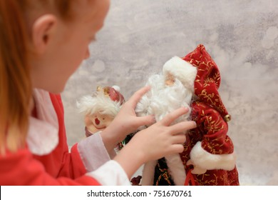 Blurred Little girl in Santa Claus suit looking intensely at Santa Claus Christmas ornament.