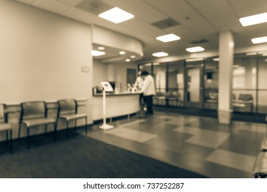 Blurred lobby/front desk area of clinical laboratory services office. Customer check-in on kiosk tablet upon arrival. Test center diagnostic testing, medical, healthcare abstract background. Vintage